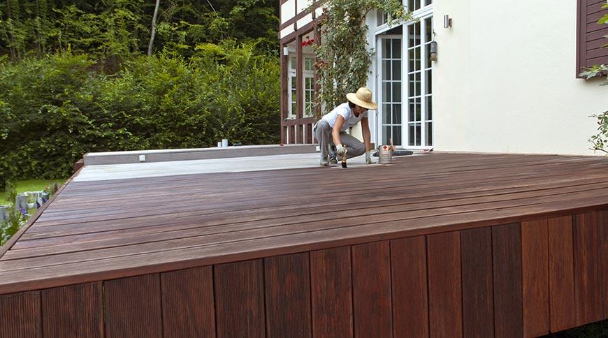 Frau streicht Terrasse mit Terrassenholzöl